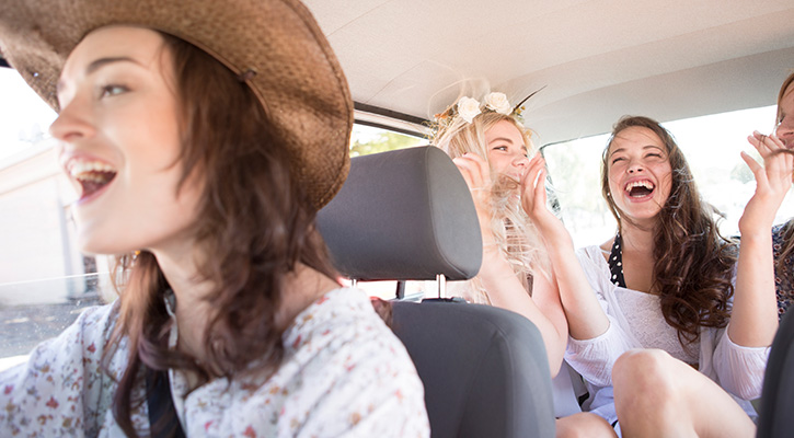 Three girls in a car, two in the back and one with a hat in the front, all of them laughing and having fun
