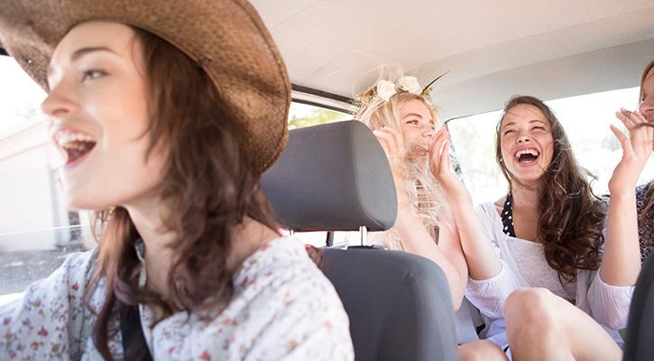 Tres chicas en un coche, dos detrás y una con sombrero delante, todas riendo y pasándoselo bien