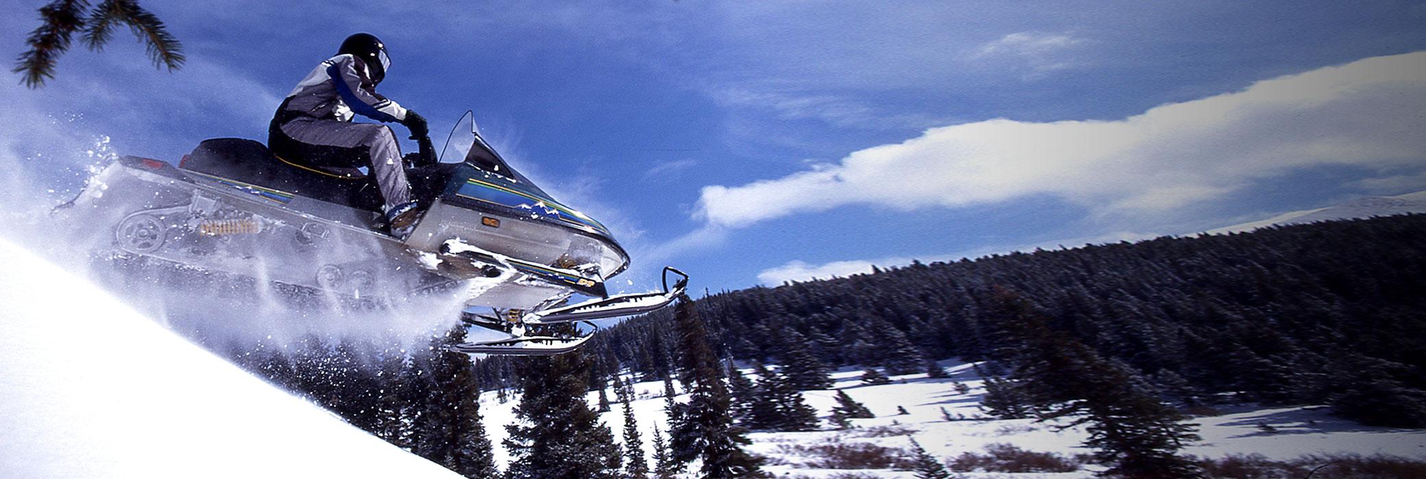 Iemand die met zijn sneeuwscooter over een heuvel vliegt, blauwe lucht op de achtergrond