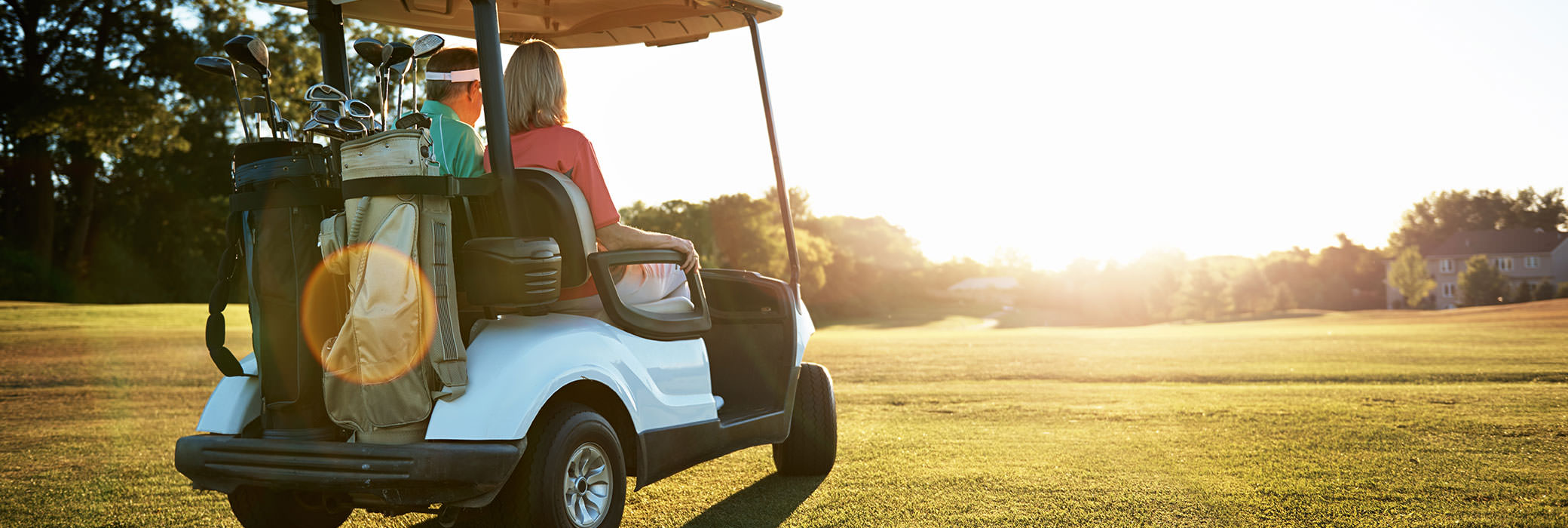 Couple sitting in a white golf cart on a golf course while it's sunny