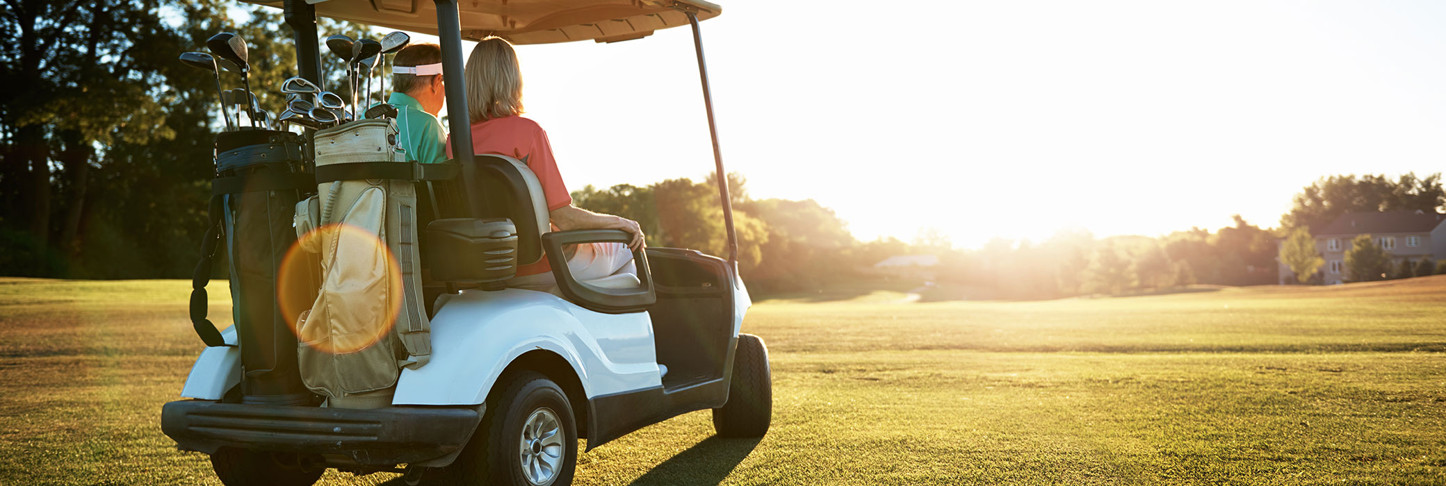 Ein Paar sitzt in einem weißen Golfwagen und fährt bei sonnigem Wetter über einen Golfplatz