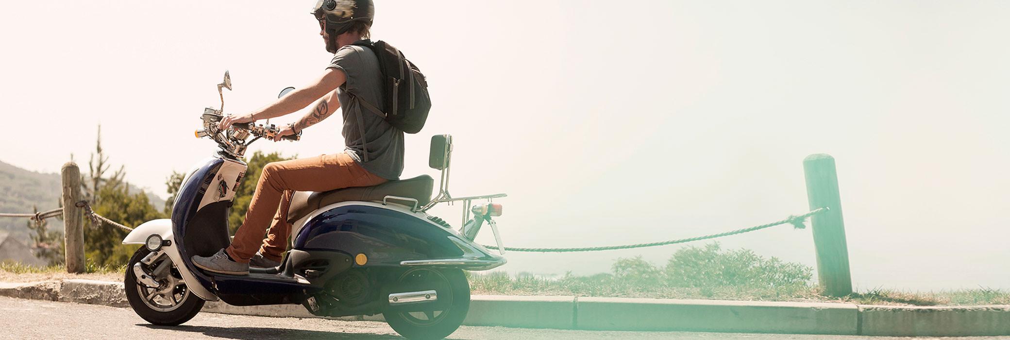 Een man op een scooter die weg van de camera rijdt