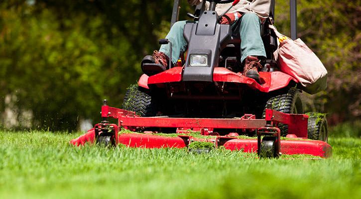 Мужчина на красной ездовой газонокосилке косит траву