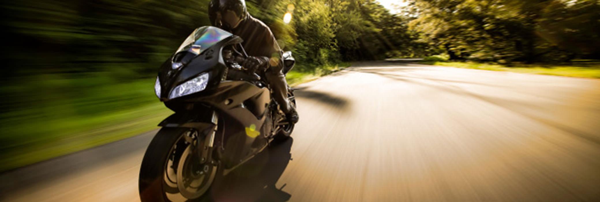 Mustapukuinen mies ajaa mustalla moottoripyörällä puiden reunustamalla maantiellä
