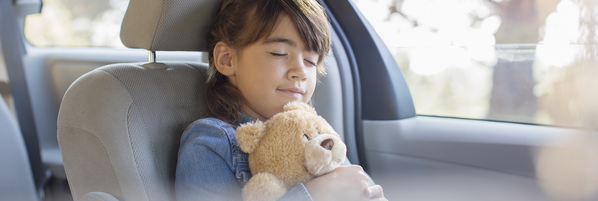 A little girl smiling and sitting in a car hugging her teddy bear with her eyes closed