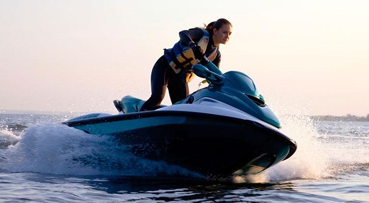 Ein Mann, der auf einem Jet Ski über das Wasser rast und nass wird