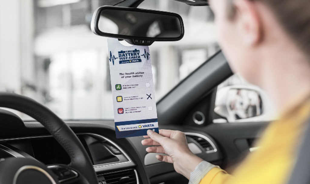 Woman sitting in her car infront of the steering wheel holding the results of the battery test in her right hand