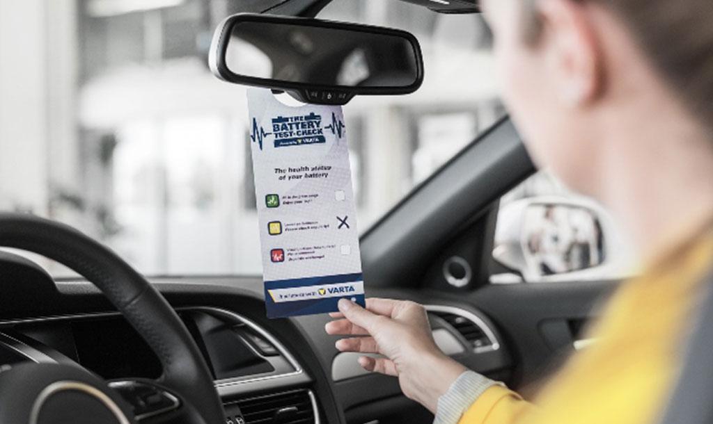 Vrouw die achter het stuur in haar auto zit en de resultaten van de batterijtest in haar rechterhand houdt