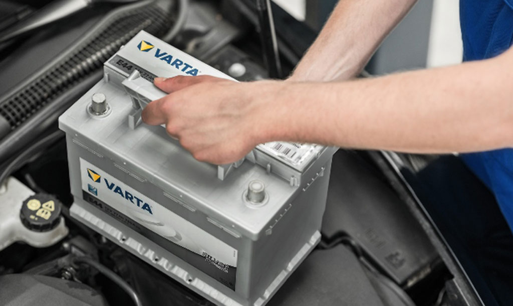 Retailer holding the battery above its correct position in the car