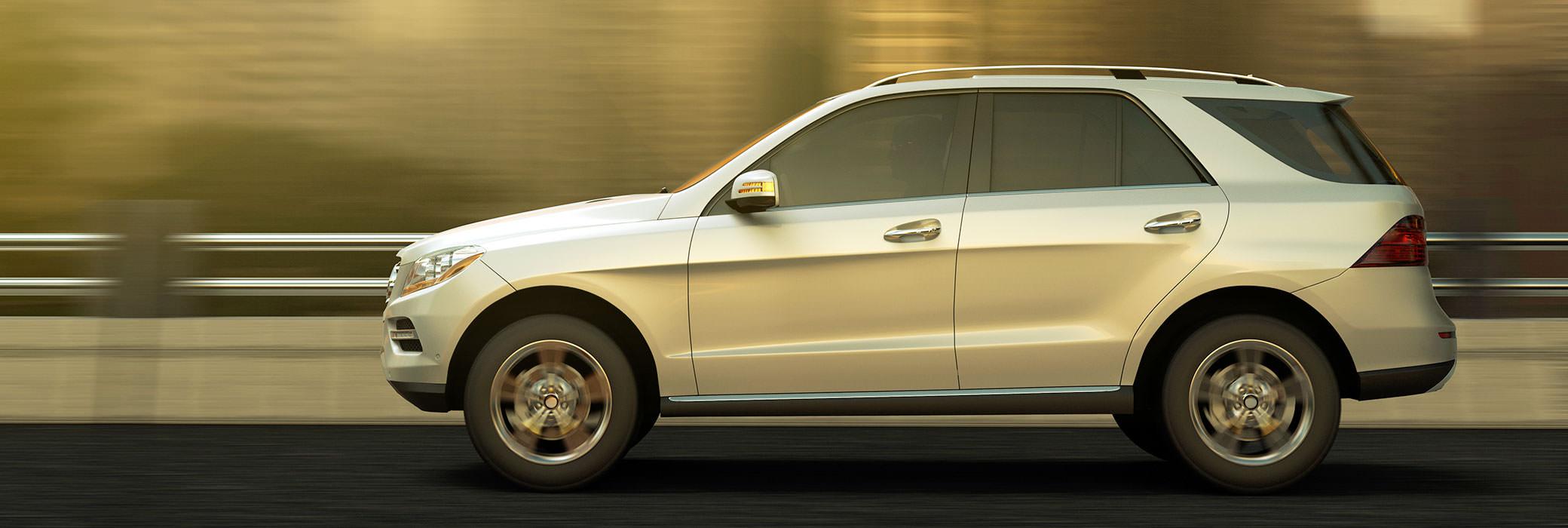 Sivunäkymä hopeanvärisestä, keskikokoisesta autosta ajamassa tiellä