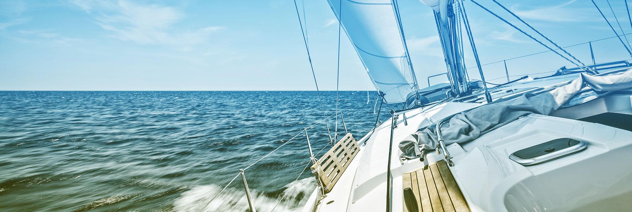 Een zeilboot in open water met blauwe lucht
