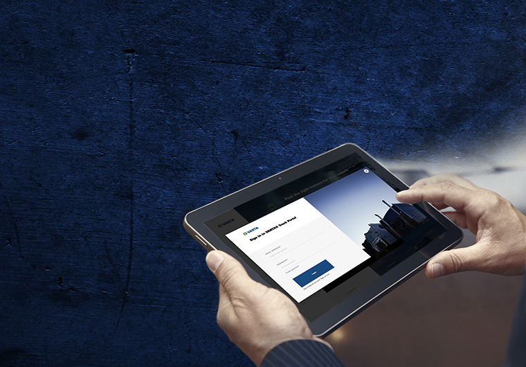 Picture of a man holding a tablet with the log-in page of the VARTA® Truck Portal