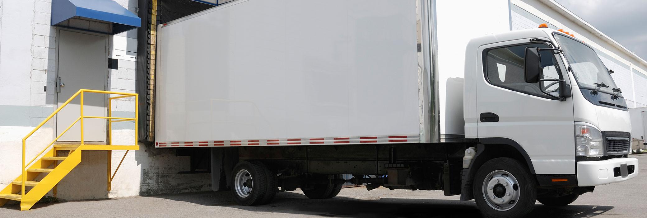 Ein weißer Lieferwagen steht vor einem Gebäude und wird beladen