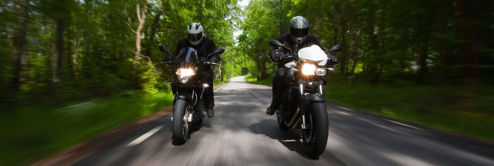 A guy in black riding his black motorcylce on a country road with trees at the sides
