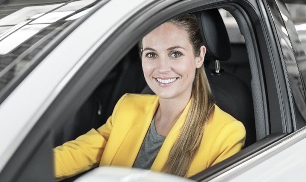 Woman is sitting in her car and smiling into the camera because she is happy about the test results