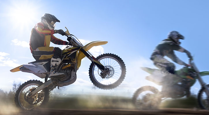 Kaksi henkilöä ajaa moottoripyörällä maantiellä