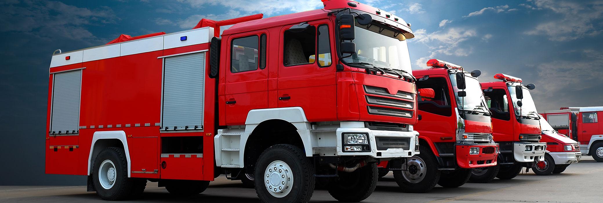 Camiones de bomberos en fila. Cielo azul nublado sobre ellos.