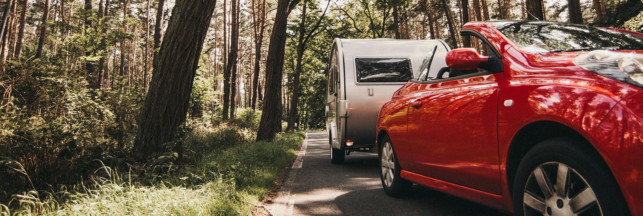 Ein rotes Cabriolet mit einem weißen Wohnwagen fährt eine Landstraße entlang