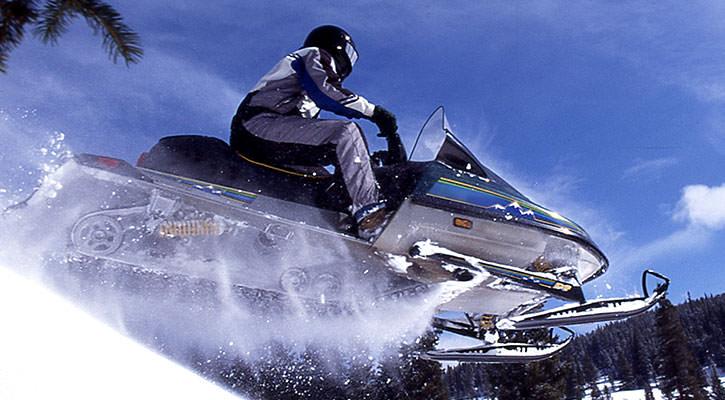 Eine Person, die mit ihrem Schneemobil vor einem blauen Himmel über einen Hügel fliegt
