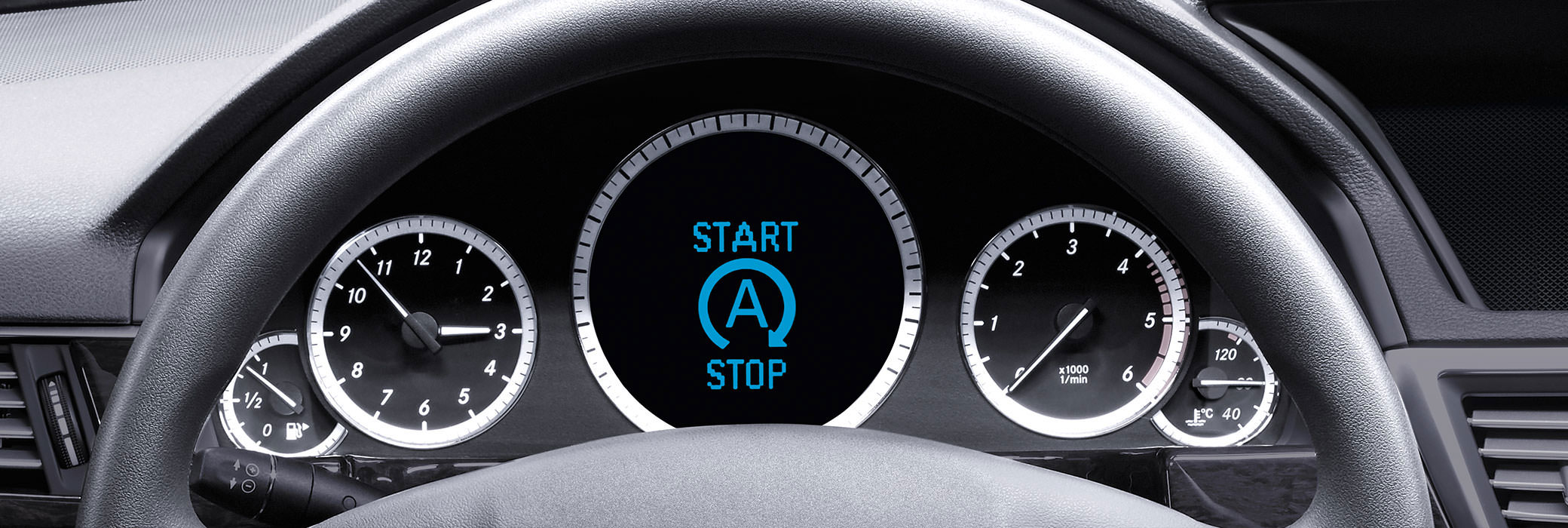 The dashboard of a car with the clock on the left side, the speed indicator on the right side and a start stop sign in the middle