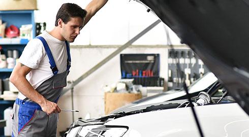 En smilende og glad fyr står foran en blå bil på et værksted