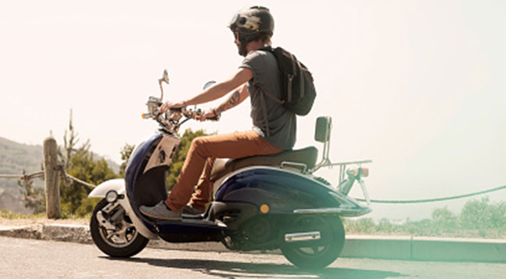 Um homem a conduzir uma scooter a afastar-se da câmara