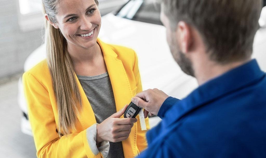 Klant (vrouw) in gele jas die sleutels van haar auto aan dealer (man) overhandigt
